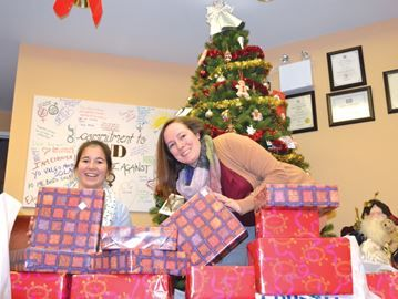 Barrie shelter's Secret Santa makes clients feel special - Women and Children's Shelter administrative assistant Kaity Fotherby and development manager Lisa Spinks-Smith unload an array of gifts an anonymous donor left for the women who will be spending Christmas in the shelter.