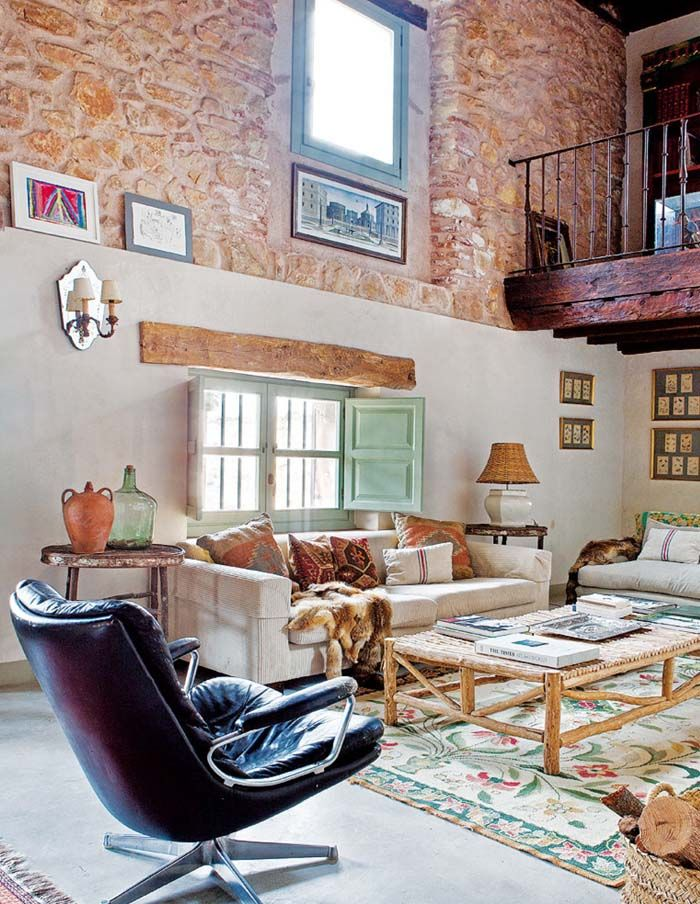 A home in Spain with exposed stone walls and a beautiful vintage rug.