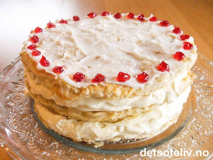 """Alle kjenner vi """"Napoleonskake"""", men kanskje best i form av klassiske, avlange porsjonskaker som fås kjøpt i konditorier. Her har du i stedet en flott """"Napoleonskake"""" laget som rund festkake! Det strides om """"Napoleonskake"""" er oppkalt etter selveste Napoleon Bonaparte eller ikke. Antakeligvis har kaken ikke noe med denne personen å gjøre, men er snarere oppkalt etter byen Napoli, som også er opphavsstedet til den italienske kaken """"Mille foglie"""" som ligner svært på kaken vi i Norge kaller ..."""