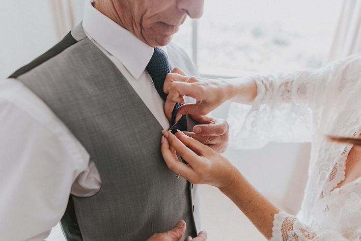 Bride helped her dad to place his tie pin right.