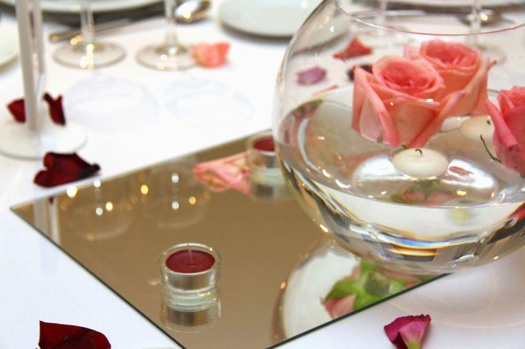 Bonita pecera de rosa rosa, con base de espejo y velitas rojas. #decoración #bodas #mesas
