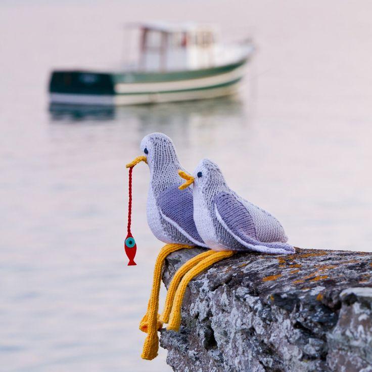 des doudous en tricot en forme de mouettes, comme des oiseaux posés sur un rocher face à la mer, en train de pêcher un poisson rouge.