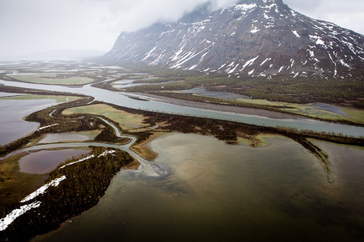 Gidágiesse.The ice has released the grip and the water is again free, while the greenery is still fighting against the snow. Photo: Carl-Johan Utsi.