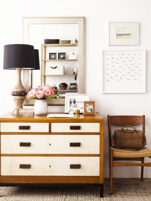 A layered vignette atop dresser drawers with vintage items, decorative accessories, and black lampshade.