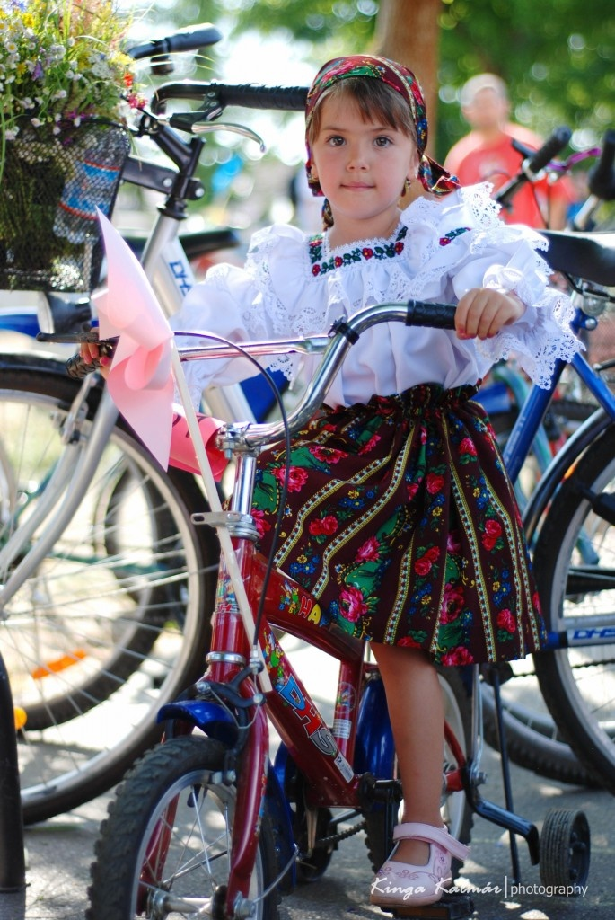 Beautiful little girl cycling in a Romanian traditional costume