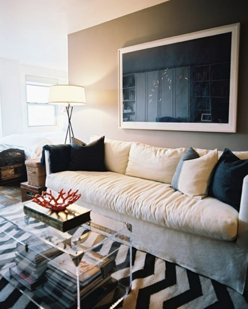 Ashley Wick - Chic, modern living room design with oatmeal fabric linen  sofa, black and white zig zag chevron rug, lucite acrylic trunk coffee table,  .