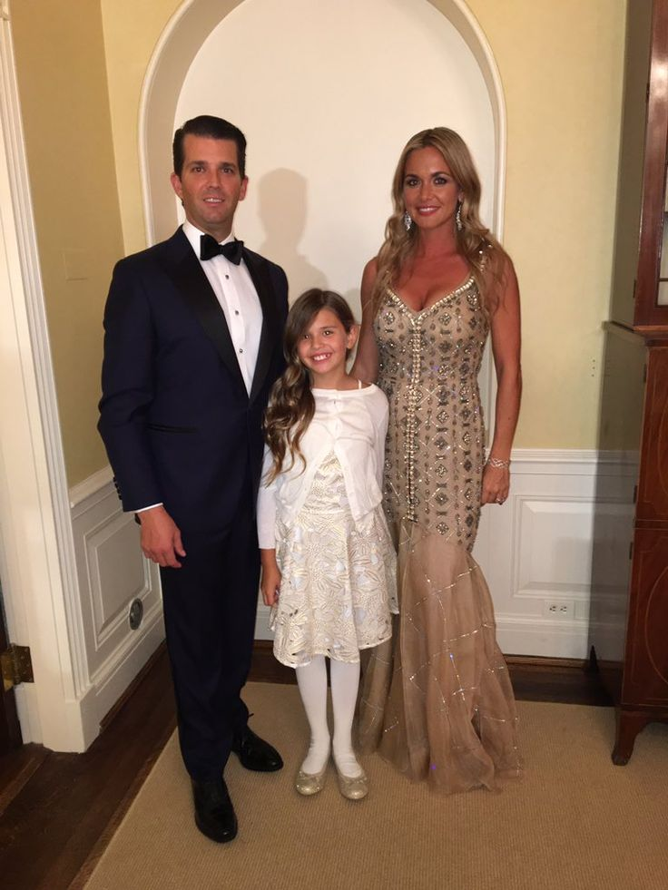 Donald Trump, Jr. and Vanessa in.a golden-tan organza Dennis Basso gown pose with their daughter Kai at the Inaugural Ball on 1/20/17.
