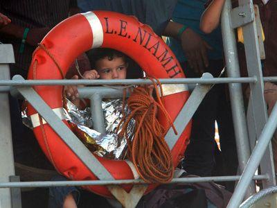 Un bambino fotografato mentre migranti si preparano a scendere dalla nave militare irlandese L.E. Niamh, appena arrivata nel porto di Messina, 29 luglio 2015 © GIOVANNI ISOLINO/AFP/Getty Images