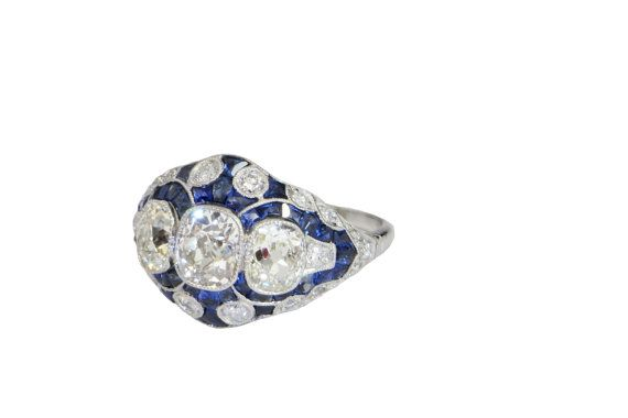 This divine platinum vivid blue sapphire and old cushion cut diamond ring is a custom made piece dating to the 1920s.  It is entirely hand