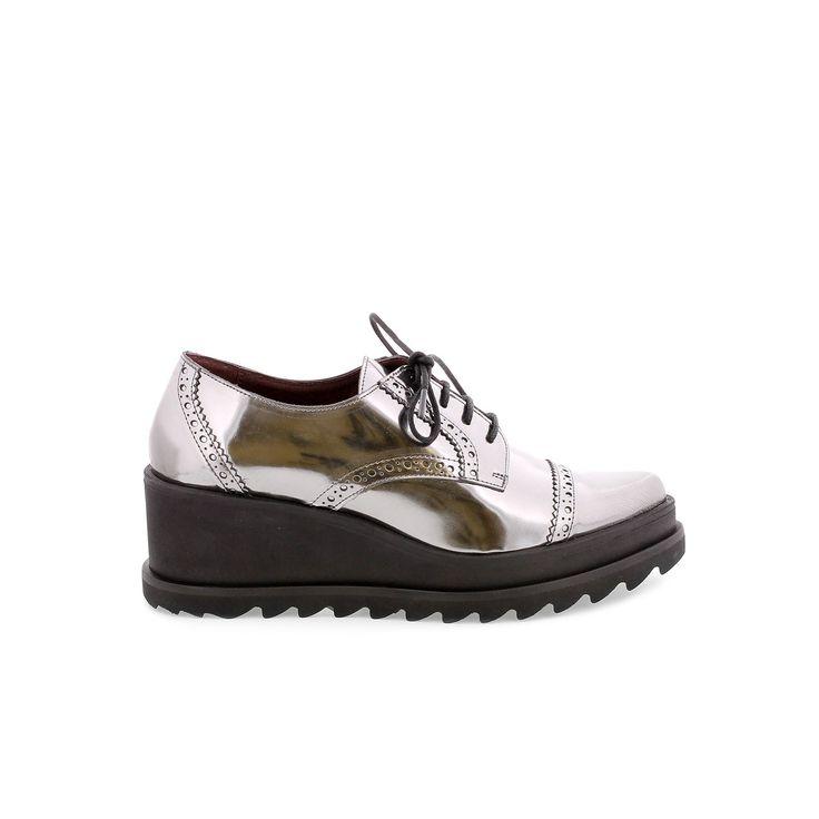 Zapato estilo blucher con cierre de cordones. Cuña exterior media y patín dentado.