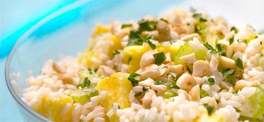 Doe de rijst in een steelpan met 50 cl kokend water. Dek af en laat 20 min. sudderen op een heel laag vuur.      Snij, ondertussen, de selder fijn en kook in 3 min. gaar in gezouten kokend water in een steelpan. Giet af, schrik in koud water en laat uitlekken.      Schil de halve ananas, snij in schijfjes en vervolgens in stukken.      Doe de chutney, honing, kerrie, mayonaise en yoghurt in een grote kom, meng met de klopper en breng op smaak met peper en zout.      Rooster de amandelen...