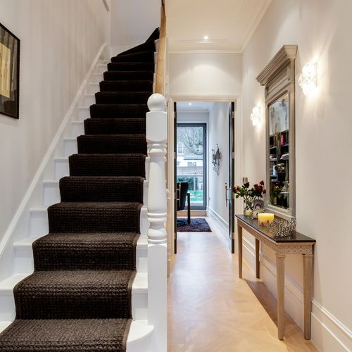 Photo of a small classic wood straight staircase in London with wood risers.