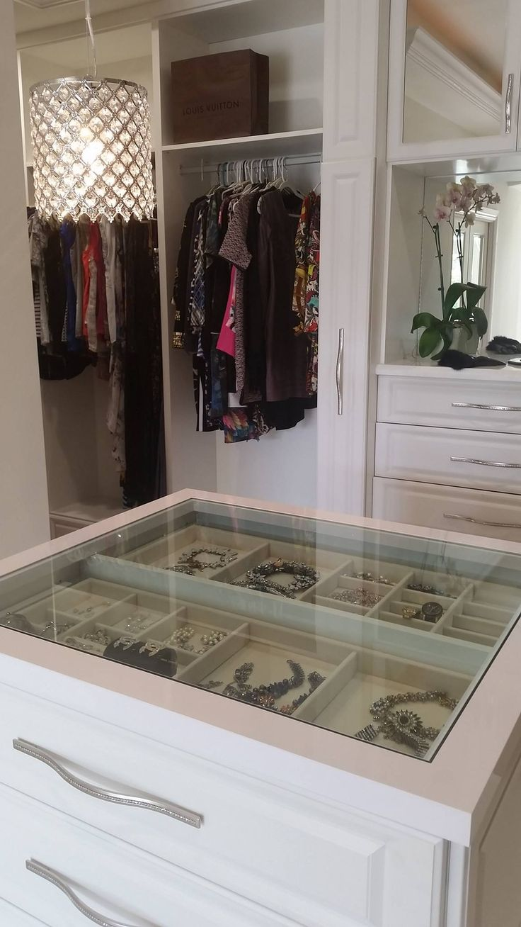 A see through center island counter top, allowing you to view your precious jewelry at a glance.    Designed by Senior Designer Jeanne Hessen  Learn more: https://www.closetfactory.com/custom-closets/