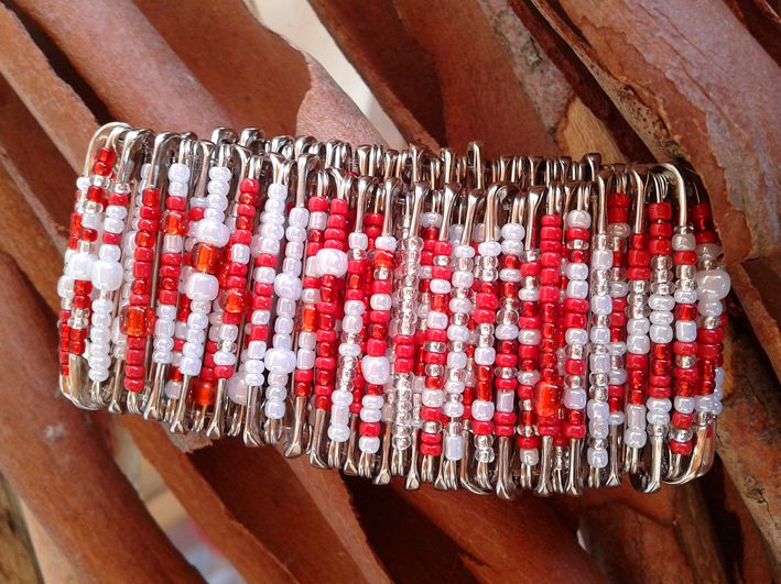 safety pins dressed with red and white beads www.valeart.gr