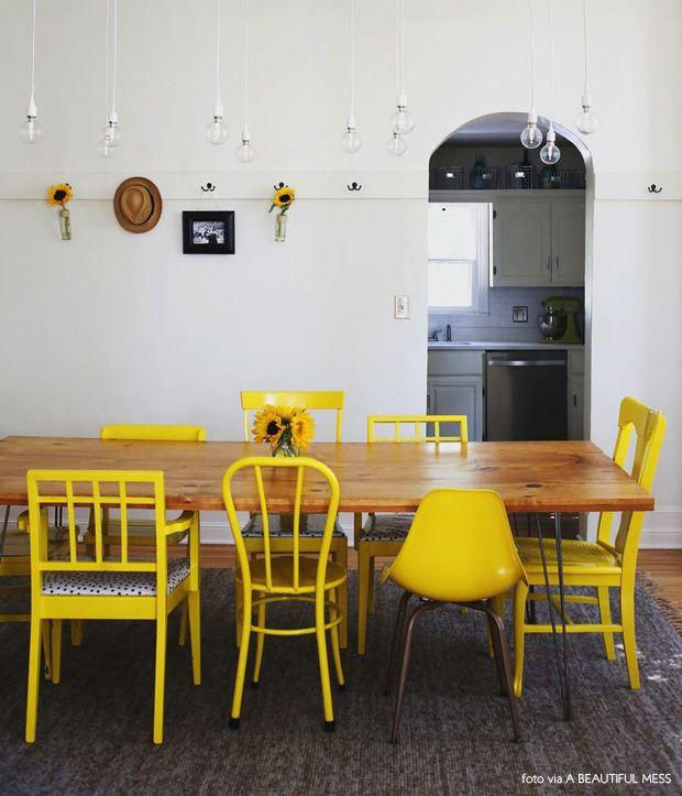 sala de jantar com várias cadeiras amarelas e lâmpadas à mostra