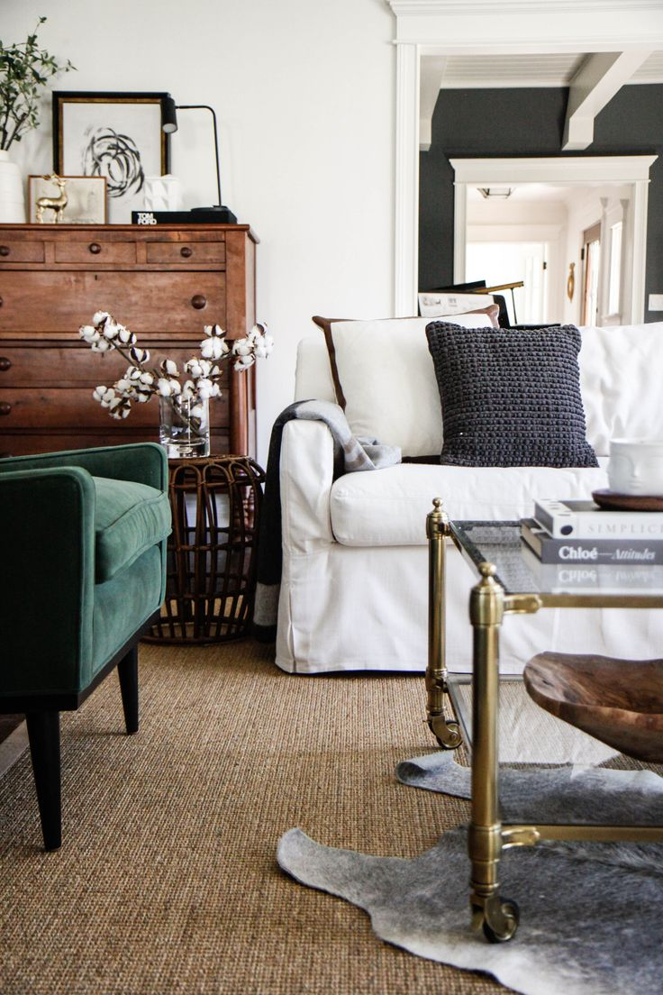 layered rugs, brass and glass coffee table on casters + green accent