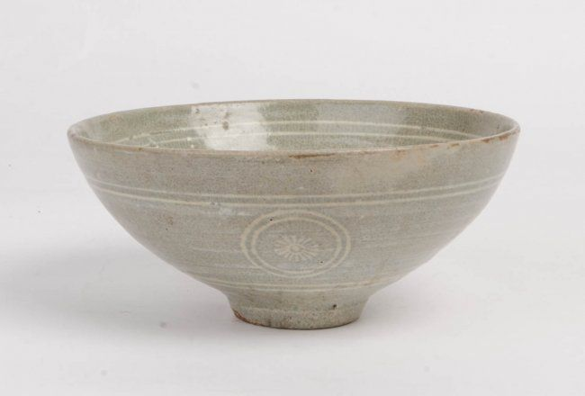 A Korean celadon bowl, Koreo Dynasty, 12th/13th century, Slip decorated with three flowers in the centre and three stylised crysanthemum roundells on the outside, finely crazed greenish-blue glaze, 8.5cm high, 18.5cm diameter