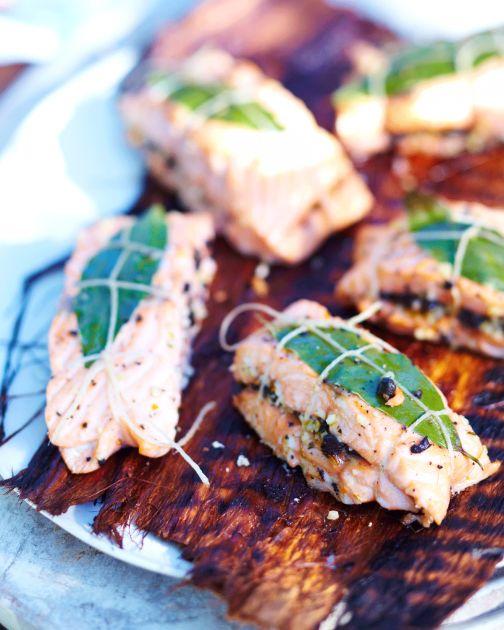 Eine Orangen-Oliven-Mischung wird auf den Fischfilets verteilt. Mit Küchengarn zu Päckchen verschnürt können die Lachsfilets auf den Grill.
