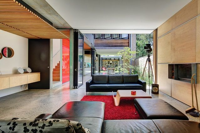 Thick service walls line the boundary, allowing living spaces to interact freely with the outdoors.