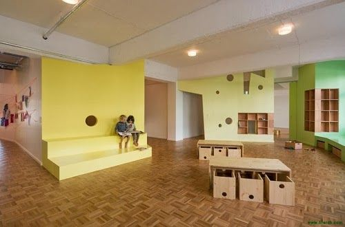 Kita Loftschloss in Berlin designed by Baukind. The space is broken into smaller areas with the use of angled walls, which is then further broken down with storage, levels and holes.