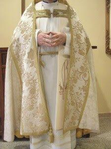 Capa Pluvial: Capa que llevan los sacerdotes o diáconos en los actos de culto divino que lleva capillo o escudo en la espalda.