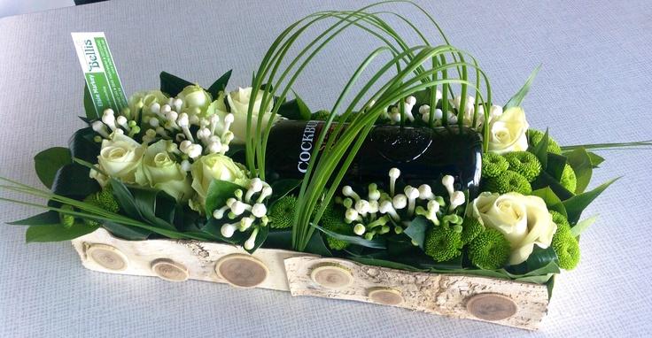 Wijnfles verwerkt in bloemstuk.