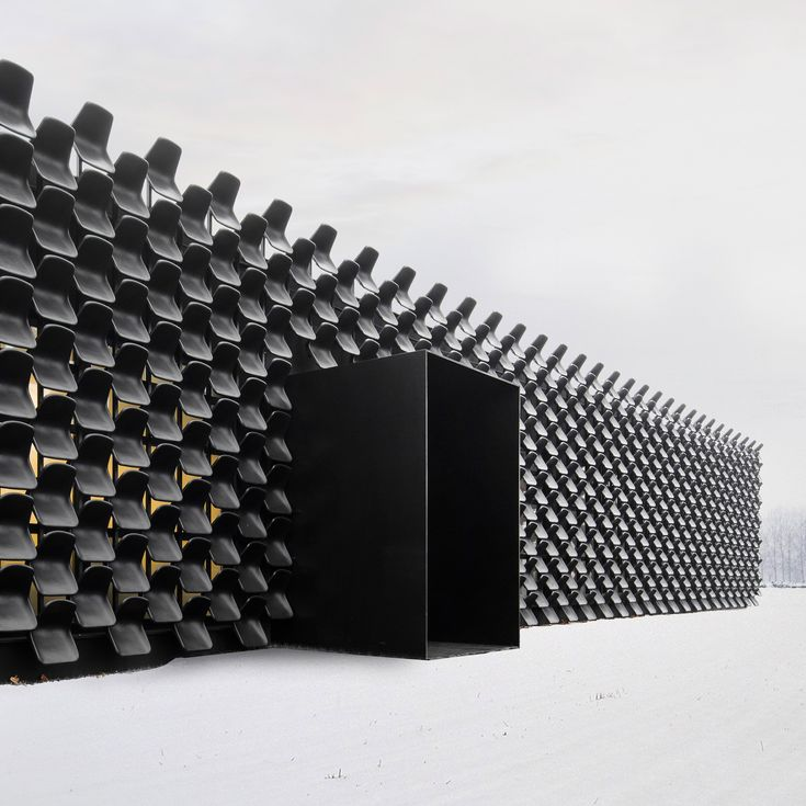 Hundreds of used black plastic chairs cover the facade of this furniture shop, which architecture studio Chybik + Kristof has created inside a former car showroom in the Czech city of Brno.
