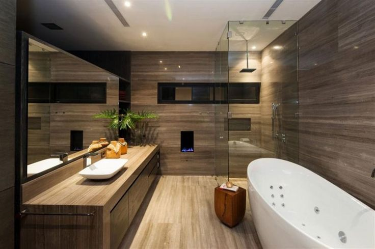 cool bathroom clad-in wood, equipped with a standalone bathtub, shower area with glass panels, a fireplace, wooden bathroom cabinet, white wash basin, modern taps and large mirror