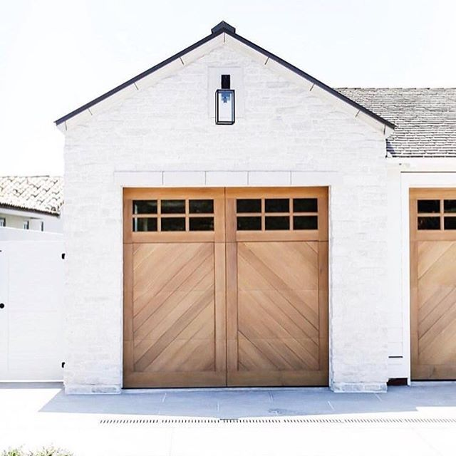 Love seeing this garage door I designed posted all over instagram. It was custom made of natural cedar wood planks in a chevron design that I had bleached and stained to get just the right color. Tumbled stone, custom lantern, cast stone, grey limestone driveway.  #tiffanyharrisdesign  @ryangarvin  Architect @brandonarchitects  Builder: #genovacustoms  #coronadelmar #orrington