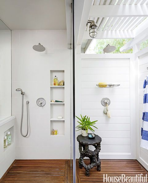 Only a glass wall separates the indoor shower on the left from the outdoor shower on the right for an uninterrupted visual flow of space in this Los Angeles bathroom designed by John De Bastiani. Fixtures by Jaclo. Outdoor light and soap dish by Restoration Hardware. Table from Dennis & Leen.