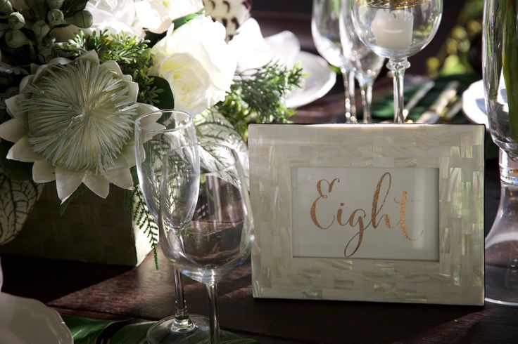 White and gold tropical wedding with mother of pearl frame for table number
