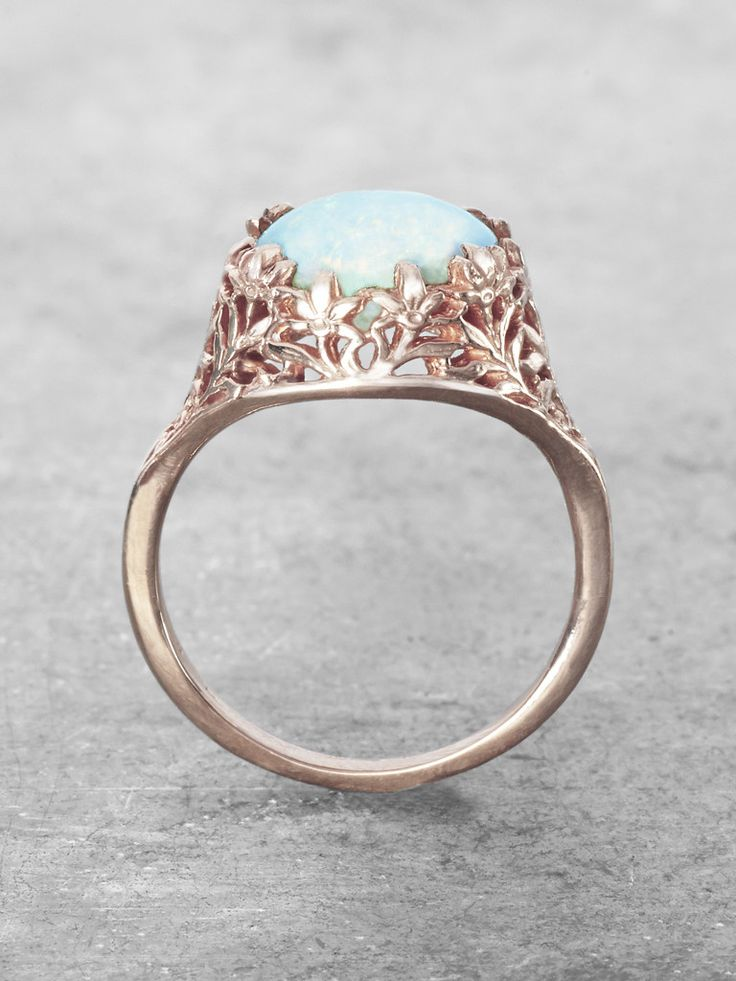 Iridescent rainbows with fiery flashes can be seen in the domed Gem of our Precious Shimmering Opal ring. Clasped in a bouquet of beautiful delicate flowers, and named for the divine goddess of flora,