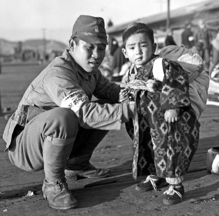 """Busan: Japanese soldier and son, December 1945. """"At the docks in Fusan, Koreans had been brought brought back to their native land and Japanese were being sent back to Japan .  The United States Military Government was in charge."""""""
