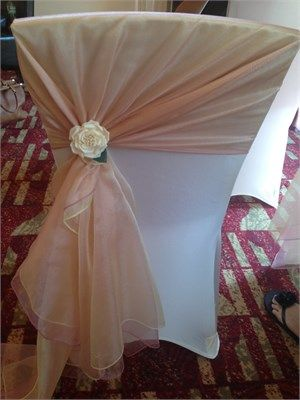 Ivory chair cover with gold and dusky pink organza sash tied on the side with a rose