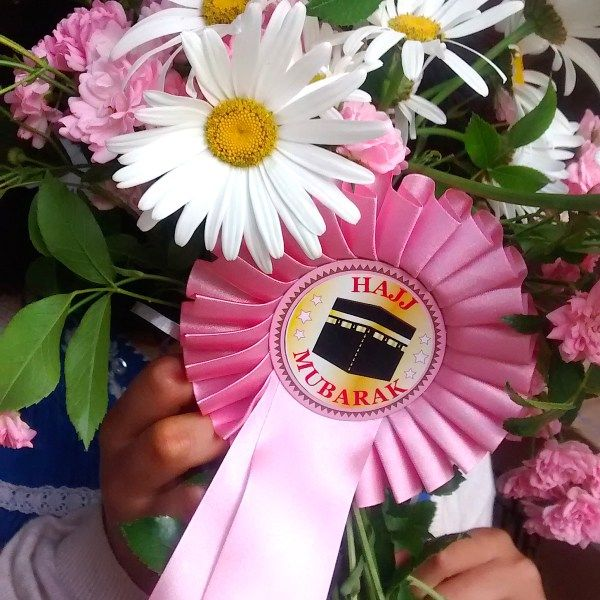 Hajj Mubarak Rosette pink  £4.50  Make your welcome home flowers super special by adding our Hajj Mubarak rosette to your bouquet!  The Hajj Mubarak rosette comes with a separate thin ribbon that you can tie around your flowers. The rosette has a metal clip on the back so you can easily attach the rosette to the thin ribbon. The size of the rosette from top to tail is 310mm , width is 115mm