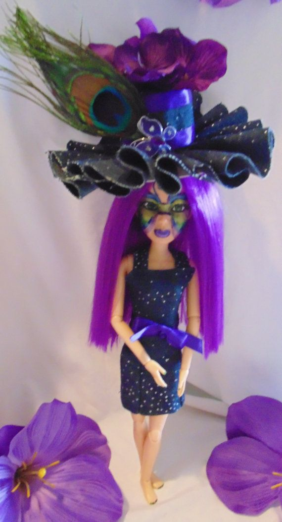 This is a liv doll repaint-  I begin with removing all of the manufacturing paint and then hand paint their faces. I have given her long purple human hair, hand painted peacock color mask, eyelashes, a fun tall custom hat(made with blue jean denim fabric with silver dots and a peacock feather (non removable). Her accessories consist of purple flowers and butterflies. I have also made her a matching blue jean denim outfit(non removable). She has peacock color painted nails and toes.