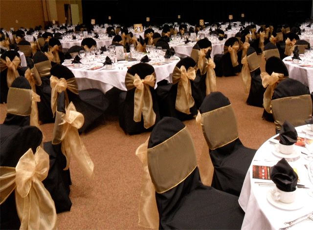 Gold Bows on black chair covers for rent - Special Event Linens.