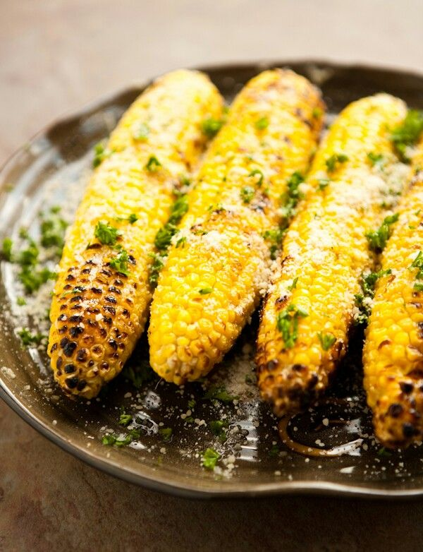 Parmesan Garlic Grilled Corn  4 ears of fresh corn 2 tablespoons butter 1 clove garlic, grated 1/4 cup freshly grated Parmesan cheese 1 tablespoon freshly chopped Italian parsley, for garnish Directions:  Preheat grill to 350° - 400°. Remove husks and silks from corn. Combine grated garlic and butter in a small bowl. Melt butter in microwave for 10 - 15 seconds on high.  Grill corn until lightly charred and deep, bright yellow (about 15 - 20 minutes). Brush garlic butter over corn and…