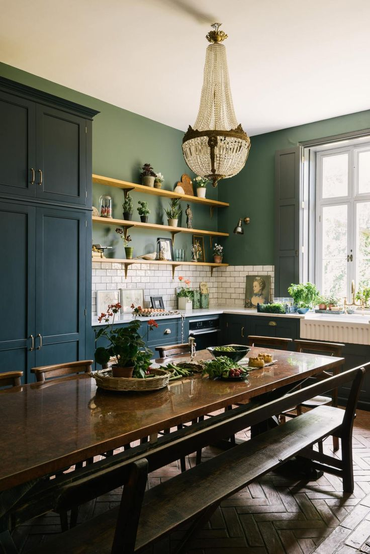 Classic blue kitchen in a Victorian rectory with terracotta floor and green walls with open shelves