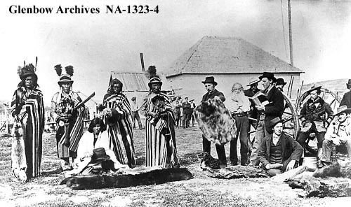 Cree men and traders at Fort Pitt, Saskatchewan. Autumn 1884  Photographer: Cote, N.O.    L-R: Four Sky Thunder; Sky Bird [or King Bird]; Matoose (seated); Naposis; Big Bear; Angus McKay; Mr. Dufresne; Louis Goulet; Stanley Simpson; Constable G.W. Rowley (seated); Alex McDonald (in back); Corporal R.B. Sleigh; Mr. Edmund; and Henry Dufresne [Bleasdell Cameron says the photo shows Corporal Sleigh and Billy Anderson; Fred Bagley claims they are Constables Patsy Carroll and H. A. Edmonds]