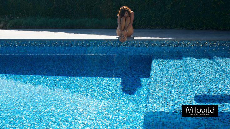 Zwembad afgewerkt met blauw glasmozaïek en gouden accenten.  Swimming pool with shades of blue glass mosaic, mother of pearl and golden tiles.
