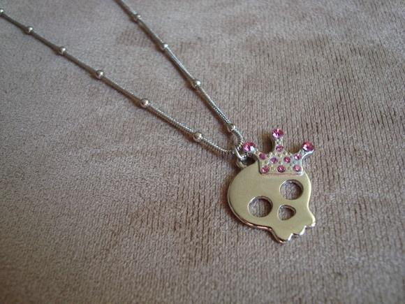 Colar em corrente de metal na cor prata e pingente de caveira com coroa, também em metal prata, com aplicação de strass Swarovski rosa. R$29,90