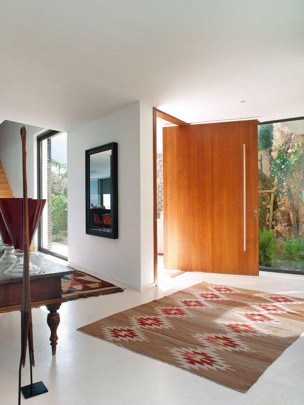 Un eje que va del dintel al suelo ancla la puerta en esta casa, diseñada por el arquitecto Miguel Ángel Lacomba.