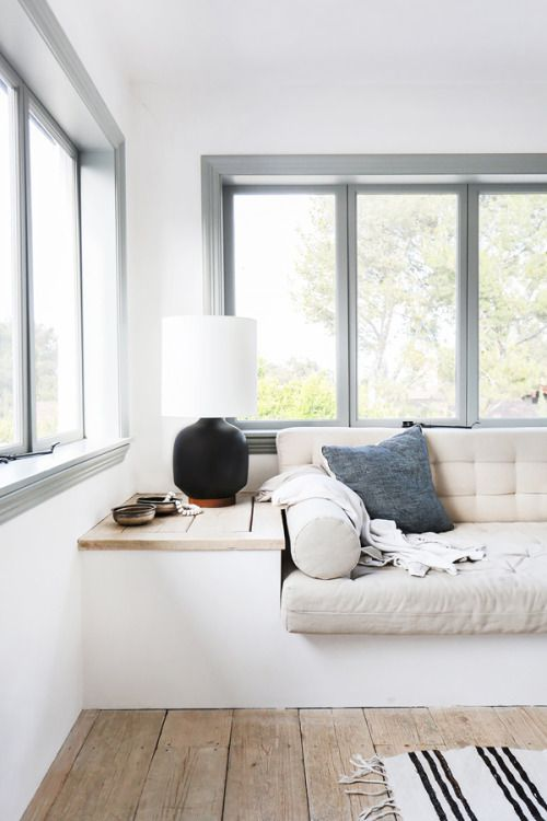 built-in seating \ window seat \ bench \ sofa \ table lamp \ light fixture \ living room \ airy \ white \ linen