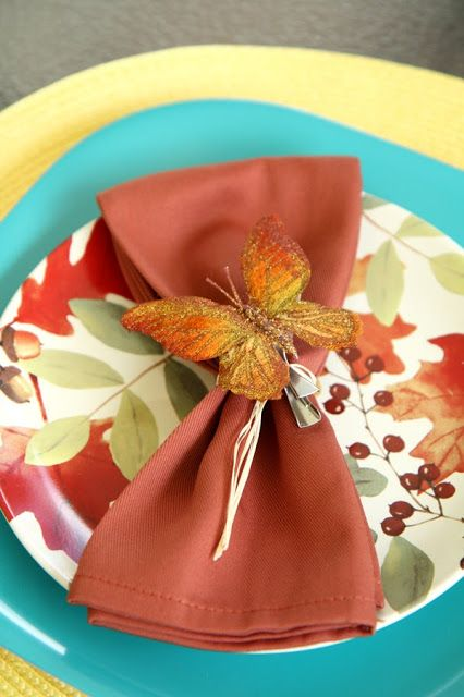 I tied some raffia around the napkins and clipped on a rust colored glitter butterfly from Michael's for a napkin embellishment.   http://southernscraps.blogspot.com/2013/09/transitional-tablescape-and-porch.html