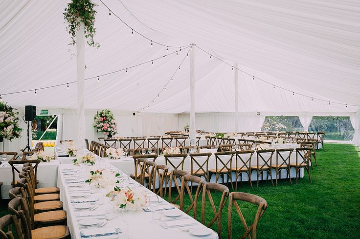 Cross back chairs in a X table arrangement. Wedding Marquee