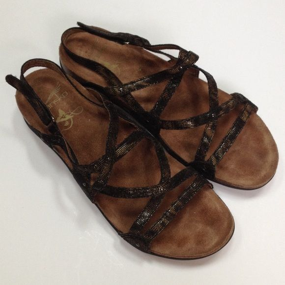 Dansko sandals This is a cute pair of Dansko sandals in excellent used condition and shows very little signs of wear. Size 40 (9.5-10). The straps are black and bronze. The base has a cork appearance. The back straps adjust by Velcro which is in excellent condition. Dansko Shoes Sandals
