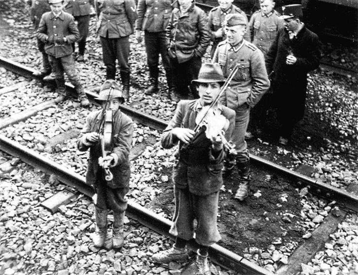 Two interned Roma boys play violins for departing and arriving detainees at a camp (possibly Beaune-la-Rolande transit camp or Pithiviers internment camp) in German-occupied France. The genocide of Roma people cost the lives approximately 220,000 to 1,500,000, most of whom died in concentration camps, with thousands more interned in camps and ghettos throughout occupied territories. France. Circa 1940-1944.