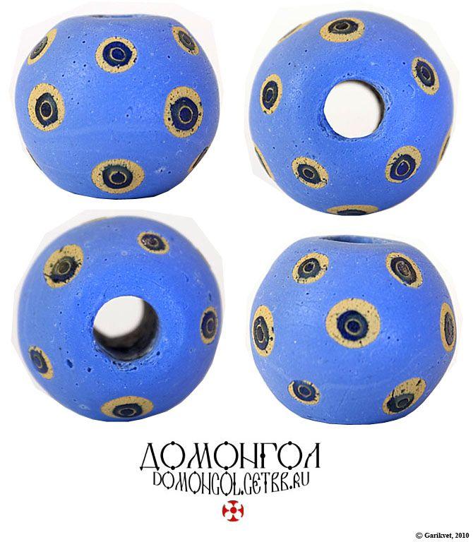 Округлая бусина ярко голубого цвета с 15 сене-желто-сине-желтыми глазками. Глазки расположены в строгой последовательности - 5 глазков обрамляют каждое отверстие канала и 5 по центру бусины, строго между верхними глазками. Синее стекло глазков прозрачно.     Размер бусины: ширина 27 мм, высота 24 мм, диаметр канала 7-8 мм.Поверхность стекла находится в прекрасном состоянии. Бусина обработана паралоидом Б 72.     Датировка дискуссионна. Не позднее 3 века н. э. domongol.org