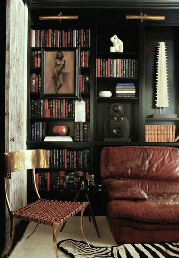 Home Library with leather sofa, zebra rug, black walls and black built-in shelving.